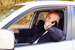 Man driving his car and speaking on the smartphone Royalty Free Stock Photos