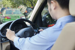 Man driving his car while texting with cellphone Stock Photos