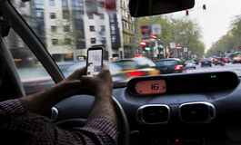 Man driving his car while using a smartphone stock photos