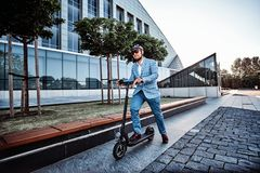Man is driving his new electro scooter near big glass building royalty free stock image