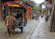 Man is driving horse-drawn vehicle  in Lijiang Royalty Free Stock Image