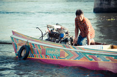 Man driving a longtail boat Stock Photos