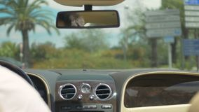 Man driving luxury car down road of resort city, transportation, directions. Stock footage stock video