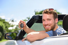 Man driving new rental car showing keys happy. Man driving rental car showing new car keys happy. Young adult excited on road trip with key for cars leasing or Stock Images