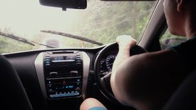 Man is driving in the rain. Young man driving a car in the rain stock footage