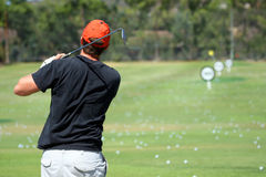 Man at the driving range. A man hitting golf balls at a driving range Royalty Free Stock Photos