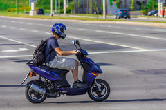 Man driving on a scooter. Man driving on low speed on a Tomos Nitro scooter in Taschereau street, Brossard, Quebec, Canada Royalty Free Stock Photography