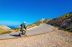Man driving scooter on road turn in mountains Stock Image