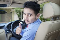 Man with in the driving seat. Looking back and showing thumb up.  Stock Photography
