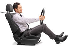 Man driving seated on a car seat. Profile shot of a young man holding a steering wheel seated on a car seat on white background Royalty Free Stock Photos