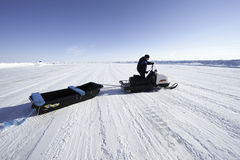 Man driving a snowmobile on a background of the vast expanses of Royalty Free Stock Photos