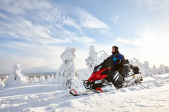 Man driving snowmobile in Finland. Man driving snowmobile in snowyfield in a sunny day. Lapland, Finland Royalty Free Stock Photos