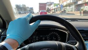 Man driving with surgical glove during COVID pandemic