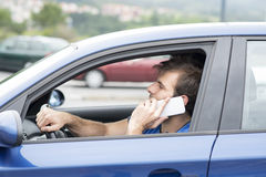 Man driving and talking by smart phone, dangerous concept. Royalty Free Stock Photos