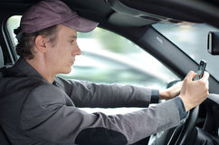 Man driving and texting someone on his cell phone. Man driving in his car using or typing on cell mobile phone, dangerous situation Royalty Free Stock Photos