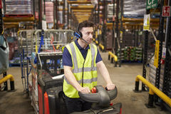Man driving a tow tractor through a distribution warehouse royalty free stock photo