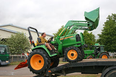 Man driving tractor. Man loading tractor on lorry Stock Photos