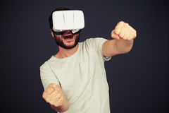 Man driving in virtual reality. Beard man driving in virtual reality wearing hi-tech VR headset, on black background stock images