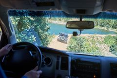 Man driving a 4WD along a dirt road. Following a friend in a second vehicle as they approach a mountain lake in a first person perspective Stock Image