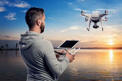 Man with drone with camera taking photos of beautiful sunset Stock Images