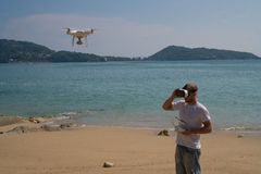 Man with drone camera and virtual reality glasses taking photos and videos on the beach Stock Photo