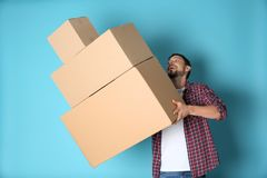 Man dropping moving boxes. On color background stock photography