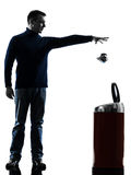 Man dropping a paper in a trash bin silhouette Royalty Free Stock Images
