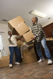 Man Dropping Stack of Boxes. Senior african american man dropping stacked moving boxes while his wife attempts to catch them stock images