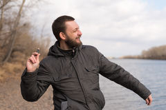 Man dropping a stone into the river Stock Photo
