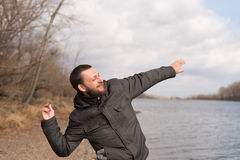 Man dropping a stone into the river Stock Photography