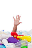 Man drowning in plastic recipients pile. Man drowning under plastic recipients pile - stretching hand for help, environment concept Royalty Free Stock Photo
