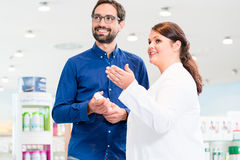 Man in drug store with sales lady shopping Royalty Free Stock Photography
