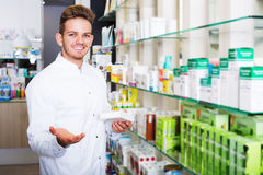 Man druggist in pharmacy. Portrait of cheerful man druggist in white coat working in pharmacy Royalty Free Stock Image