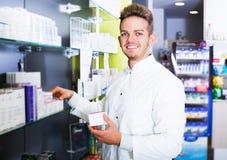 Man druggist in pharmacy. Portrait of cheerful man druggist in white coat working in drugstore Stock Photo