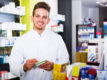 Man druggist in pharmacy. Portrait of happy man druggist in white coat working in pharmacy Royalty Free Stock Image