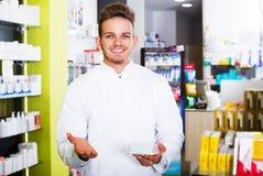 Man druggist in pharmacy. Portrait of happy man druggist in white coat working in drugstore Stock Photos