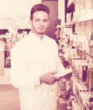 Man druggist in pharmacy. Portrait of positive man druggist in white coat working in pharmacy Stock Photos