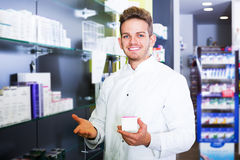 Man druggist in pharmacy. Portrait of positive man druggist in white coat working in drugstore Stock Photography