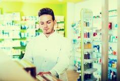 Man druggist in pharmacy. Portrait of smiling men druggist in white coat working in drugstore Royalty Free Stock Photo