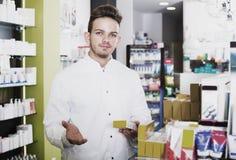 Man druggist in pharmacy. Portrait of smiling man druggist in white coat working in pharmacy Royalty Free Stock Photo