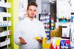 Man druggist in pharmacy. Portrait of smiling man druggist in white coat working in pharmacy Royalty Free Stock Image
