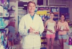 Man druggist in white coat working in pharmacy. Portrait of glad men druggist in white coat working in pharmacy Stock Photo