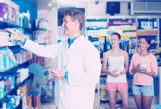 Man druggist in white coat working in pharmacy. Portrait of smiling men druggist in white coat working in pharmacy Royalty Free Stock Photography