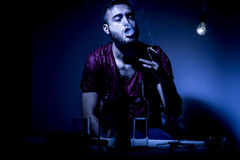 Man on drugs. Young man with beard, lost in the vices of alcoholism, smoking and drug addiction Stock Image