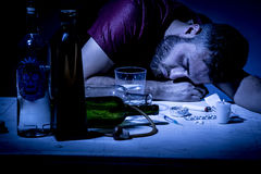 Man on drugs. Young man with beard, lost in the vices of alcoholism, smoking and drug addiction Royalty Free Stock Images