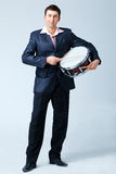 Man With Drum. Man in suite is playing on the drum with drumsticks, full length Royalty Free Stock Photography