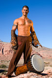 Man with drum. Full length shot of muscular man, standing on a rock next to his drum stock photos