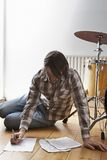Man BY Drum Kit Writing Music On Floor Royalty Free Stock Images