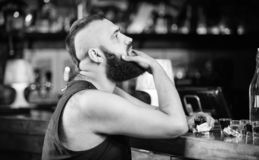 Man drunk sit alone in pub. Alcoholism and depression. Alcohol addicted concept. Hipster brutal man drinking alcohol. Ordering more drinks at bar counter. Guy stock images