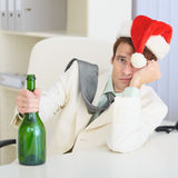 Man drunkard celebrates Christmas with wine bottle. The young drunkard celebrates Christmas with a wine bottle royalty free stock image